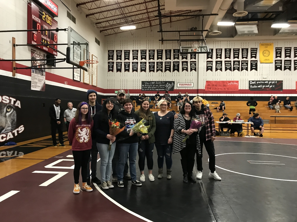 Student wrestlers with their families standing in a school gym.